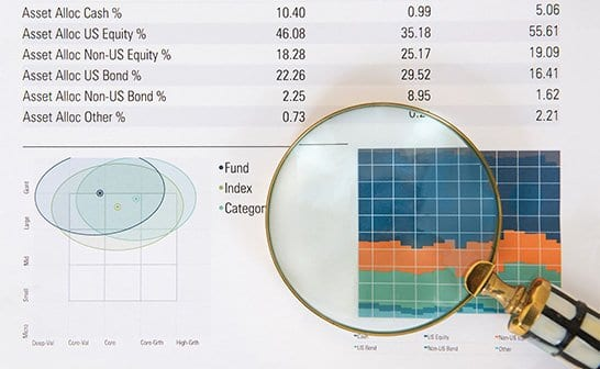 Magnifying glass looking at financial report